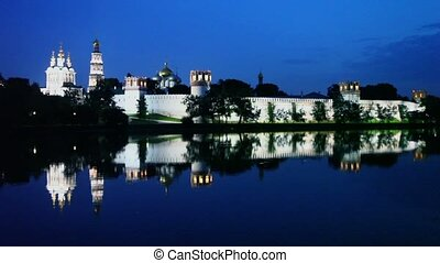 Complex of Novodevichy Convent with illumination beyond wall...