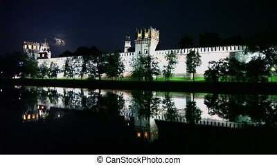 People walk near wall of Novodevichy Convent with illumination