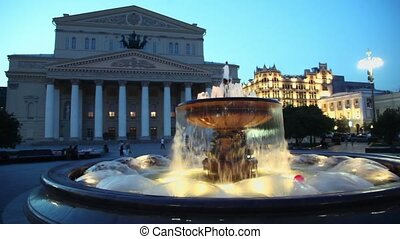 People walk near fountain with night illumination beside Bolshoy theater edifice and GUM