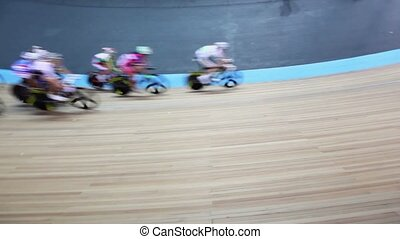 Bicyclists ride by track turn during race in stadium, show...