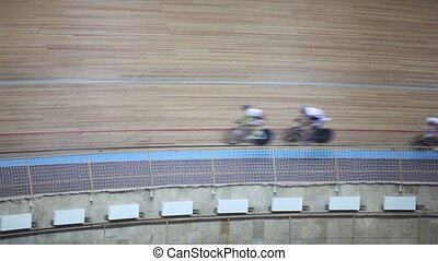 Several of bicyclists pass by track during race in gymnasium