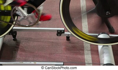 Cyclist spins pedals on bike at one place in rollers frame -...