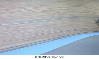 Group of bicyclists approach and pass by track during race...
