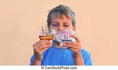 boy looks at models of tall ships in bottles and moves them...