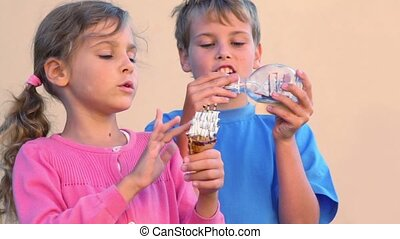 girl and boy plays with models of tall ships in glass...