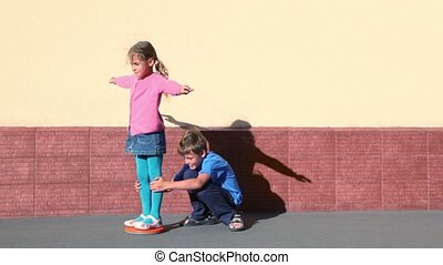 Boy rotates girl which spins with arms up sideward near wall...