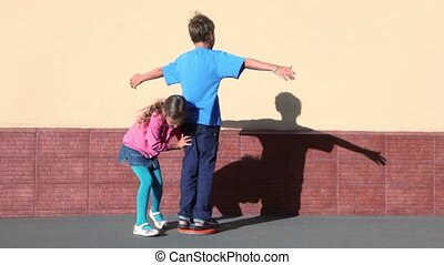 girl rotates boy which spins with arms up sideward near wall...