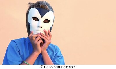 Little boy holds two masks near faces and then removes them...