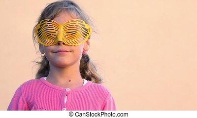 girl wears glasses in form of butterfly and then removes them