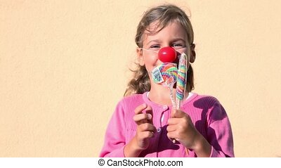 girl with clown nose holds candies and choose which one to eat
