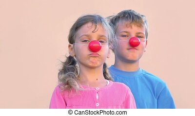 Two kids boy and little girl with clown noses smile and blink