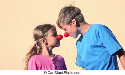 Two kids boy and little girl with clown noses play together