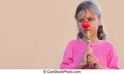 Little girl with clown nose eat colourful candy and smile
