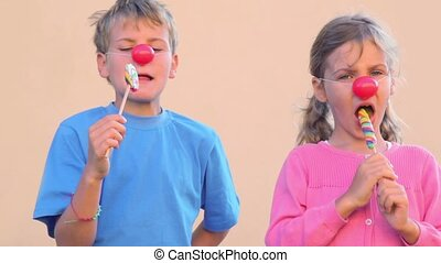 Two kids with clown noses eat colourful candies - Two kids...