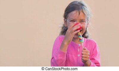 Little girl with clown nose sock colourful candy and smile
