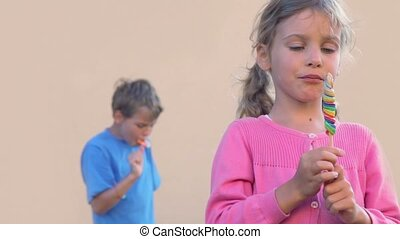 Little girl eats colourful candy and brother does same...