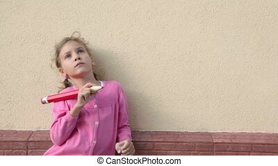 Little girl hold big pencil and think near brick wall