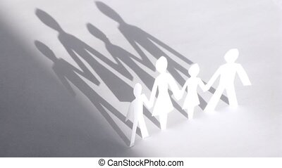 Figures of family cut from paper hold hands in sunlight,...