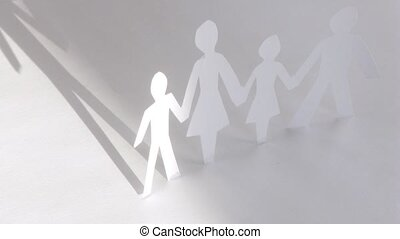 Shadow from paper figures of family lies on white background