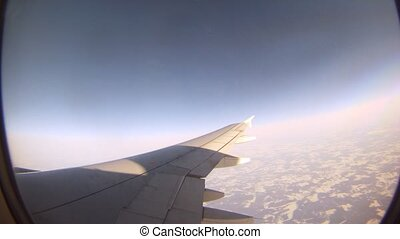 From window of flying plane is visible sunlight and Earth