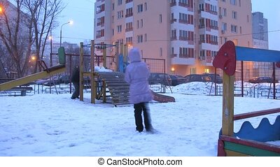 Boy and girl play in playground town in winter, time lapse