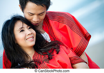 An in love young couple in romantic emotion with similar red dress