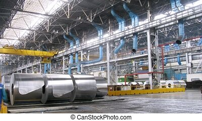 Big rolls of aluminum stand in production shop of rolling...