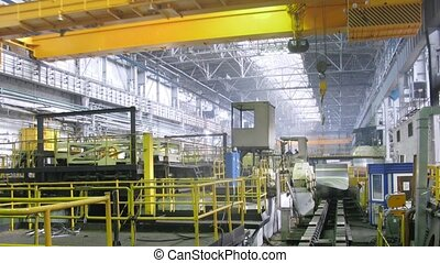 Yellow crane moves from above in production shop of rolling mill, time lapse