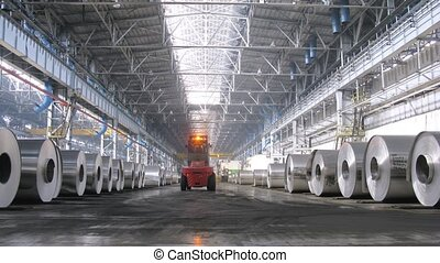 Loader distributes aluminum rolls in shop on rolling mill,...