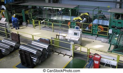 Roll of aluminum rotates on machine in workshop on plant