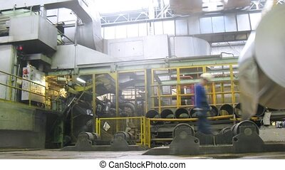 Loader lifts an roll of aluminum in production shop, time...
