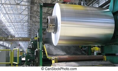 Roll of aluminum rotates on machine in workshop on rolling...