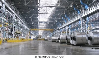 Rolls of aluminum lie on floor in production workshop of plant