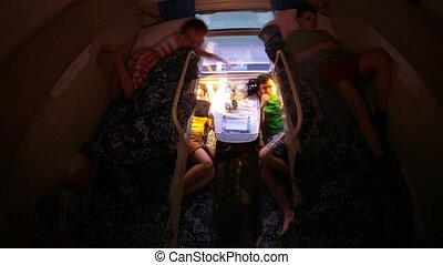 Family from four people is in dark compartment in train,...