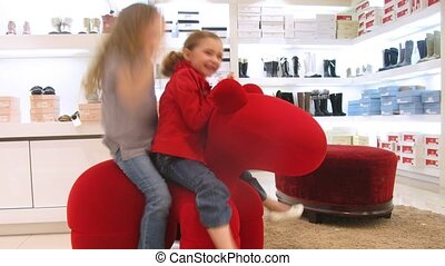 Two girls sit on chair in form of horse also hold balloons -...