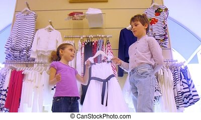 Boy helps to choose dress to sister in shop, time lapse