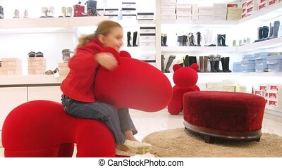 Two girls sit on chair in form of horse of red color, time...