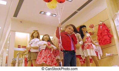 Girl holds balloons with helium in hand, time lapse