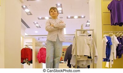Boy chooses clothes in shopping center, time lapes
