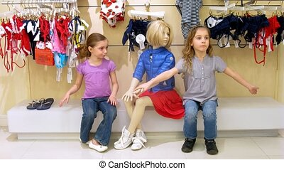 Two girls and boy sit near dummy in shopping center, time...