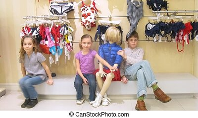 Two girls and boy sit near manikin in shopping center