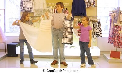 Boy helps to choose dress to girls in shop, time lapse