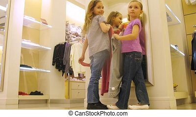 Girls try on clothes in front of mirror in shopping center,...