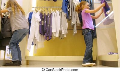 Girls try on clothes in shopping center, time lapse