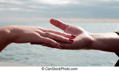 Hands with a ring - caucasian couple's hands with a diamond...