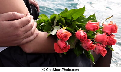 Couple with bunch of fresh flowers at the sea