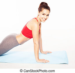 Smiling woman doing press-ups - Smiling fit young woman...