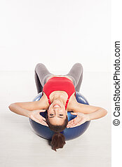 Beautiful woman doing pilates exercises leaning over...