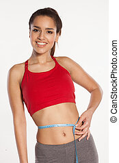 Woman measuring her waist with a smile