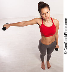 Athletic woman working with dumbbells - High angle view of...